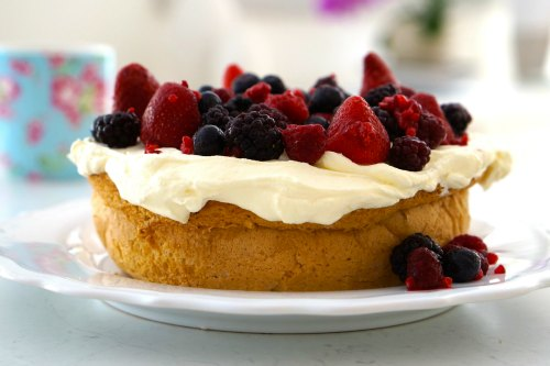 Gluten Free Cake topped with fresh cream and mixed berries
