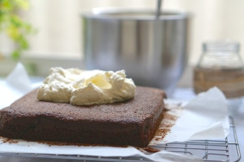 Adding the cream topping to The Best Gluten Free Chocolate Cake